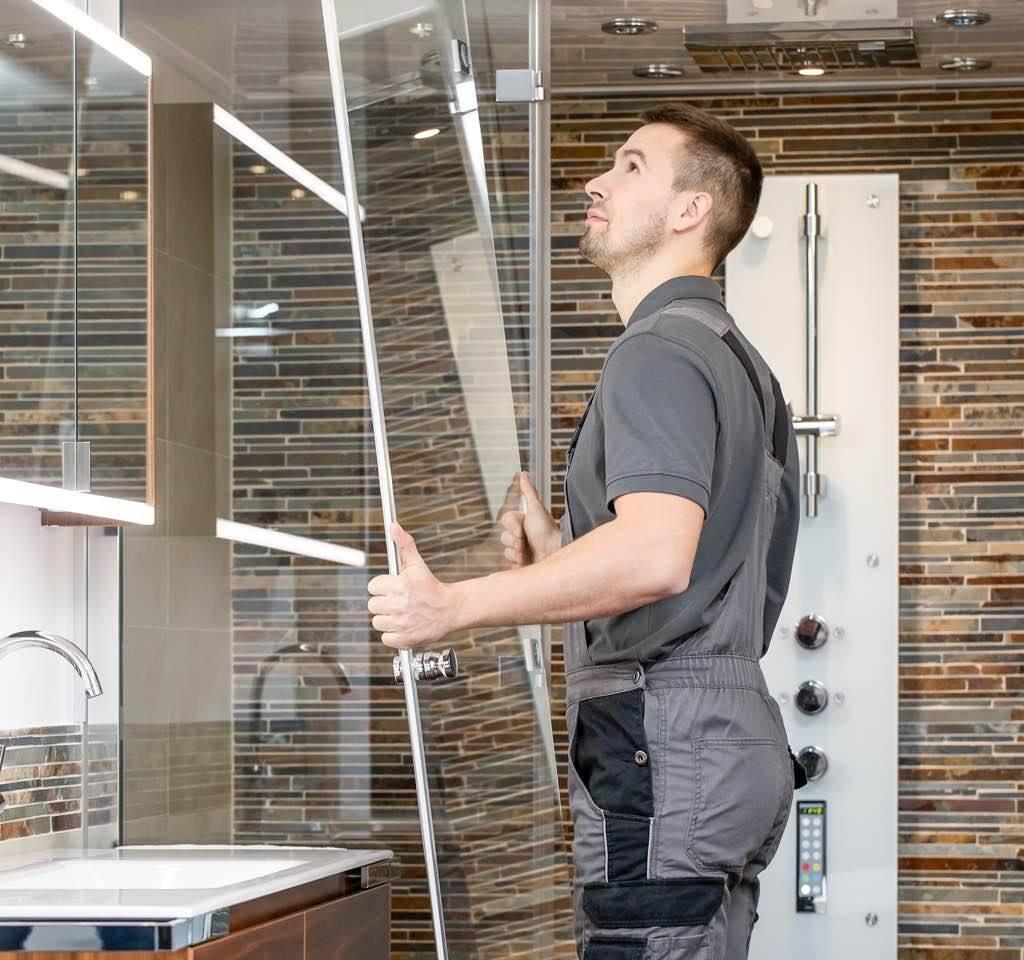 Installateur montiert Duschwand für Wellnessdusche